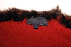 Empty clothing label. Empty labels in a red woolen sweater with fake furry neckline Stock Image