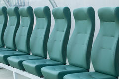 Empty coach and reserves green bench on a football stadium Royalty Free Stock Images
