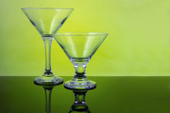 Empty cocktail glasses. Pair of glasses on green background Royalty Free Stock Images
