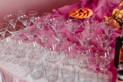 Empty cocktail glasses stand on pink and white tablecloth Stock Image