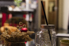 Empty cocktail jar. With a black straw and dead flowers on a table in a dining room Royalty Free Stock Image