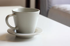 Empty Coffee Cup. An empty coffee cup on a white coffee table with a light blue sofa in the background Royalty Free Stock Photography
