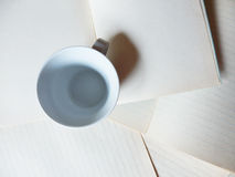 Empty coffee cup and blank paper sheets Stock Photo