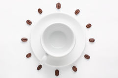 Empty coffee cup and coffee beans against white background forming clock dial viewed from top Stock Images