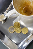 Empty coffee cup with euro coins. Capuccino in a white cup with euro coins Royalty Free Stock Photos