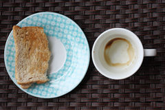 Empty coffee cup and half toast Stock Photography