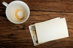 Empty coffee cup and old paper photo frame on wood background Stock Photo