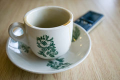 Empty coffee cup and phone Stock Images