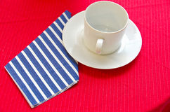 Empty coffee cup on red tablecloth. Empty white coffee cup with blue and white striped napkin on a red tablecloth Royalty Free Stock Photos