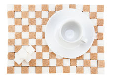 Empty coffee cup on a saucer with four white sugar cubes on a st. And of white and brown sugar. Isolated on white Royalty Free Stock Photos