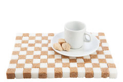 Empty coffee cup on a saucer with three brown sugar pieces on a. Stand of white and brown sugar. Isolated on white Royalty Free Stock Photography