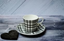 Empty coffee cup or tea cup on the plate and on the wooden table with black wooden heart royalty free stock photo