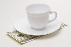Empty coffee cup and 100 USD. Close-up Stock Photo