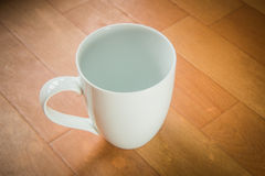 Empty coffee cup. On wooden floor royalty free stock image