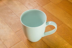Empty coffee cup. On wooden floor royalty free stock photo