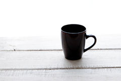 Empty coffee cup on a wooden table over white backgroun Stock Photos