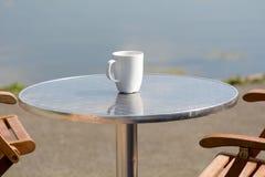 Empty coffee mug on cafe table. Besides lake Stock Photography