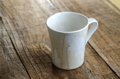 Empty coffee mug, with stains on wooden background. Royalty Free Stock Images