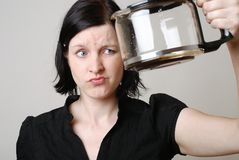 Empty coffee pot. A beautiful brunette woman looks disappointed at the empty coffee pot Royalty Free Stock Photos