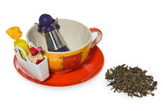 Empty coffee, tea cup with purple silver infuser in the shape of a girl on a chain. Storage on candy and two sweets, spilled tea. Royalty Free Stock Images