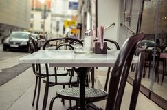 Empty coffeehouse tables. European city scene, empty sidewalk coffeehouse tables Royalty Free Stock Photo
