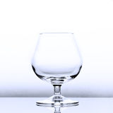 An empty cognac snifter in slightly blue light with a reflection Stock Photos