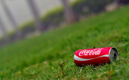 An empty coke can on lush green grass Stock Image