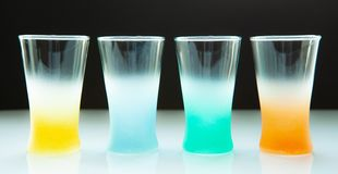 Empty colored glasses for different drinks on a dark background royalty free stock photography