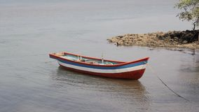 Empty colored wooden fishing boat anchored off the coast stock video