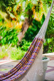 Empty colorful cloth and rope hammock hanging by the garden patio Royalty Free Stock Photography