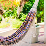 Empty colorful cloth and rope hammock hanging by the garden patio square composition Royalty Free Stock Photo
