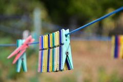 Empty colorful clothes pegs on string in garden Stock Photos
