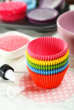 Empty colorful cupcake cases on the white wooden background Royalty Free Stock Photos
