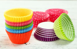 Empty colorful cupcake cases on the white wooden background Stock Image