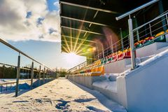 Empty Colorful Football (Soccer) Stadium Seats in the Winter Covered in Snow - Sunny Winter Day with Sun Flare. Concept of Winter Sports and Game stock photos
