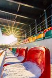 Empty Colorful Football (Soccer) Stadium Seats in the Winter Covered in Snow - Sunny Winter Day with Sun Flare. Concept of Winter Sports and Game stock photo