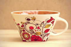 Empty colorful mug on a wooden table over grunge brown backgroun Stock Photos