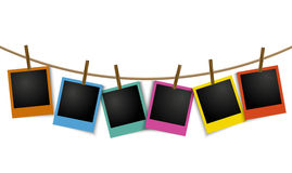 Empty colorful photo frames hanging on rope with pin Stock Photos