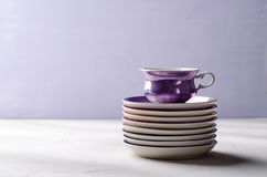 Empty colorful porcelain tableware. Violet cup with plates on lilac background Stock Photo