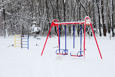 Empty Colorful Swing in Winter Time with Snow Outdoor. Children Playground In Public Park Covered With Winter Snow Stock Image