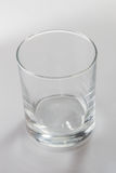 Empty colorless glass on white background. Empty colorless glass standing on white background Stock Photo