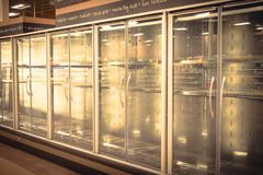 Empty commercial fridges at grocery store in America. Sold out frozen food section. Vintage tone stock photography