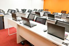 Empty computer classroom with monitors on top of table Stock Photos