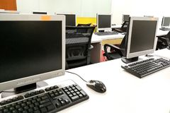 Empty computer classroom with monitors on top of table Stock Photography