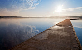 Empty concrete pier and raising sun Stock Image