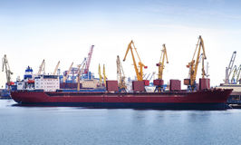 Empty container ship in port, cargo cranes on background Royalty Free Stock Photo