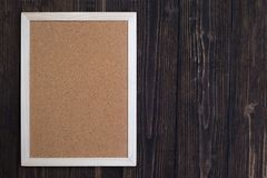 Empty cork board with wooden frame on wooden desk, top view with Stock Photos