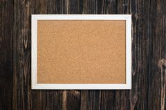 Empty cork board with wooden frame on wooden desk, top view with Royalty Free Stock Photo