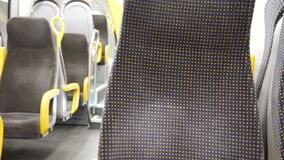 Empty corridor and seats in modern train. Wagon. Black and yellow colored stock footage