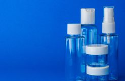 Empty cosmetic plastic bottles. Empty cosmetic plastic transparent bottles on blue background, close up royalty free stock images